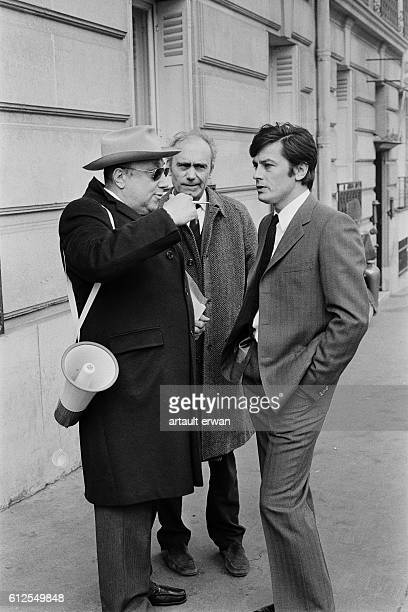 French actors Paul Crochet and Alain Delon with director and screenwriter JeanPierre Melville on the set of his movie Un Flic