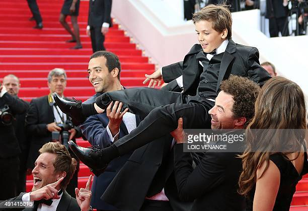 French actors Philippe Lacheau Tarek Boudali and Gregoire Ludig carry actor Enzo Tomasini next to French actress Alice David as they arrive for the...