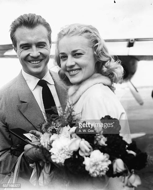 French actors Philippe Lemaire and Jeanne Moreau getting ready to leave England following the premiere of their film 'The Parasites' London Airport...