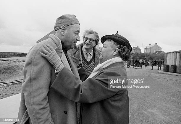 French actors Philippe Noiret and Simone Signoret talk while French director Bertrand Tavernier looks on behind them They are on the set of Pierre...