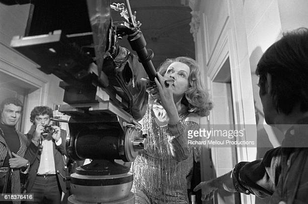 French actress and director Jeanne Moreau stands with a camera on the set of the 1976 film Lumiere a romance movie which she is both directing and...