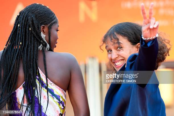 French actress and film director Mati Diop flashes the victory sign as she arrives with Senegalese actress Mama Sane for the screening of the film...
