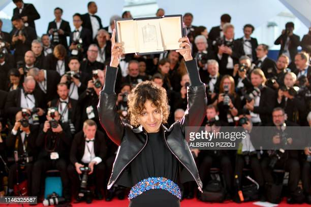 TOPSHOT French actress and film director Mati Diop poses during a photocall with her trophy after she won the Grand Prix for her film Atlantics on...