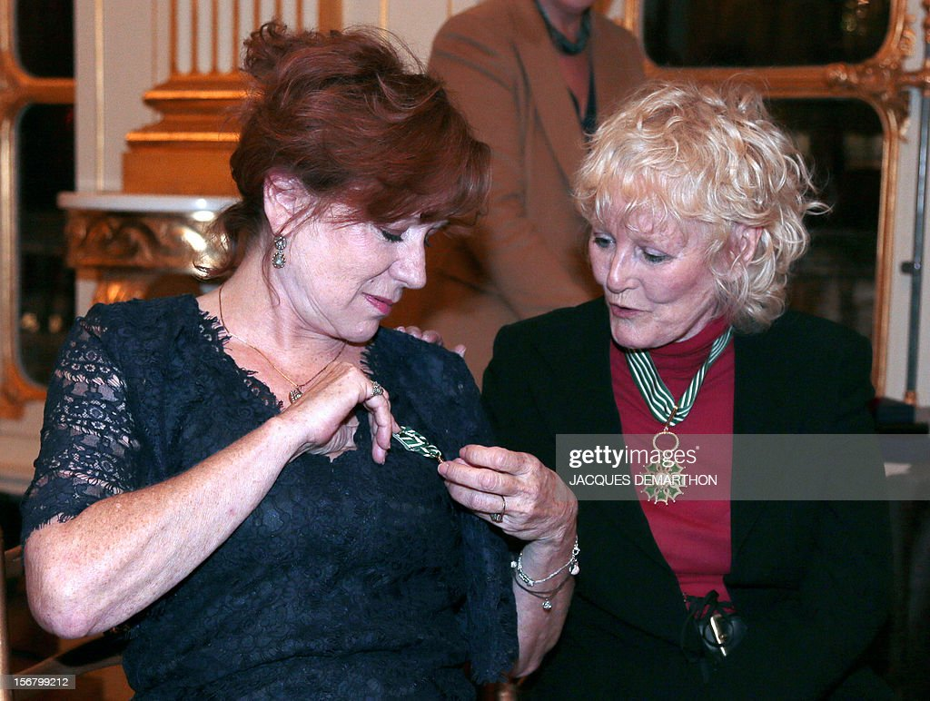 French actress and film maker Eva Darlan (L) shows her decoration to British singer Petula Clark (R) looks on after they were awarded as Knight for Darlan and Commander for Clark, in the Order of Arts and Letters during a ceremony at the ministry of Culture in Paris, on November 21, 2012. DEMARTHON