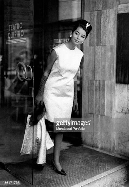French actress and model Jacqueline Sassard posing at the entrance of the Teatro Quirino wearing an elegant sleeveless dress from the new autumn...