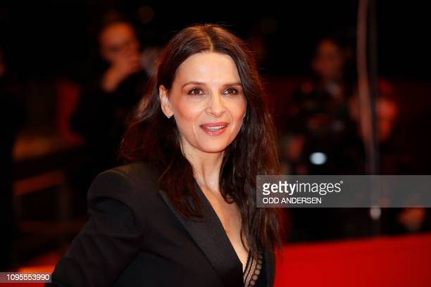 French actress and president of the Berlinale jury Juliette Binoche poses for photographers as she arrives on the red carpet for the premiere of the...