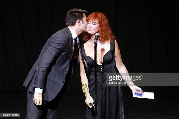 French actress and president of the jury Sabine Azema is kissed by Angouleme's mayor Xavier Bonnefont on August 26 2014 in Angouleme during the...