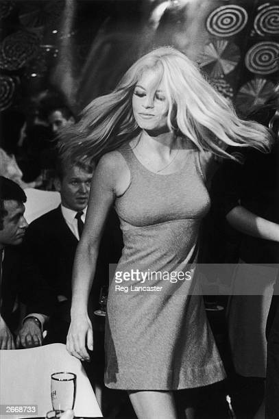 French actress and sex symbol Brigitte Bardot stage name of Camille Javal dancing in a scene from the film 'Two Weeks In September' with Mike Sarne