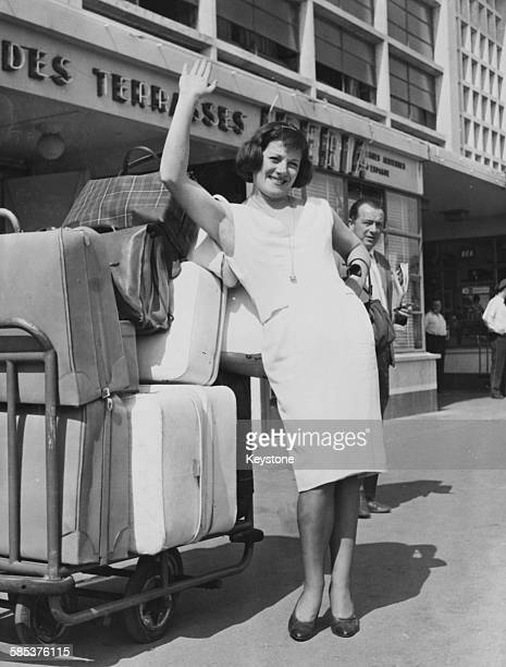 French actress and singer Colette Renard waving as she arrives with piles of suitcases at Bourget Airport on her way to Moscow with her husband and...