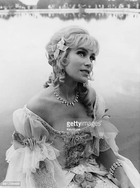 French actress and singer Estella Blain by the pond in the gardens at Versailles during the filming of 'Angélique et le Roy' France 17th August 1965