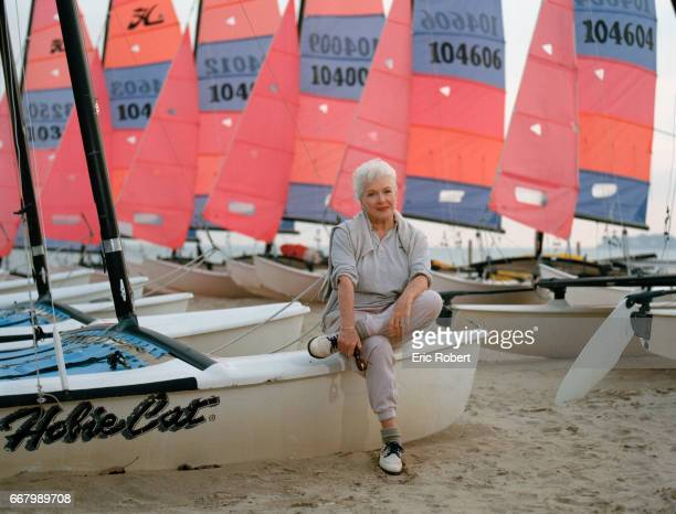 French actress and singer Line Renaud sits with rows of Hobie Cat catamarans at a beach in La BauleEscoublac France