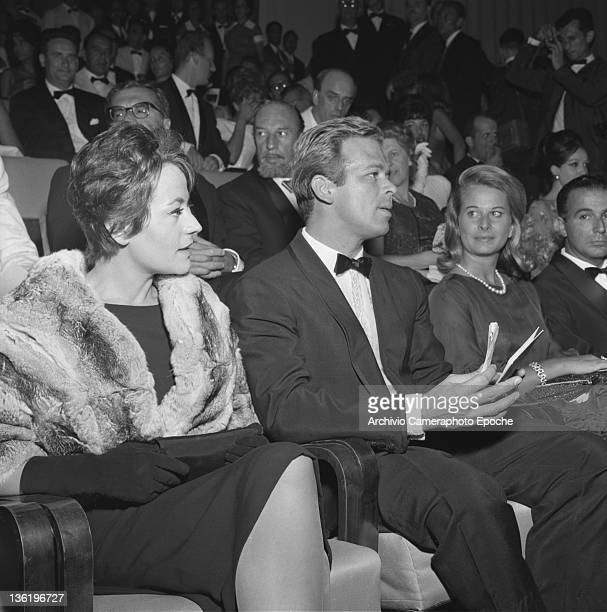 French actress Annie Girardot sitting in the first row at a movie premiere with her husband Renato Salvatori Venice 1962