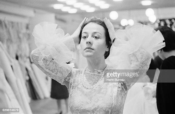 French actress Annie Girardot with Marc Bohan trying on a Dior wedding dress for costuming in the stageplay Apres la Chute written by Arthur Miller...