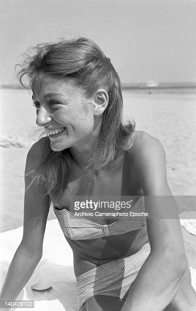 French actress Anouk Aimee portrayed while sitting on a towel on the Lido beach, Venice, 1952.