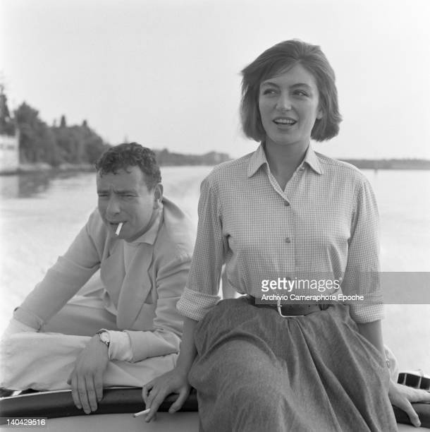 French actress Anouk Aimee portrayed while smoking a cigarette with her husband Alexandre Astruc, sitting on a boat, Venice, 1955.