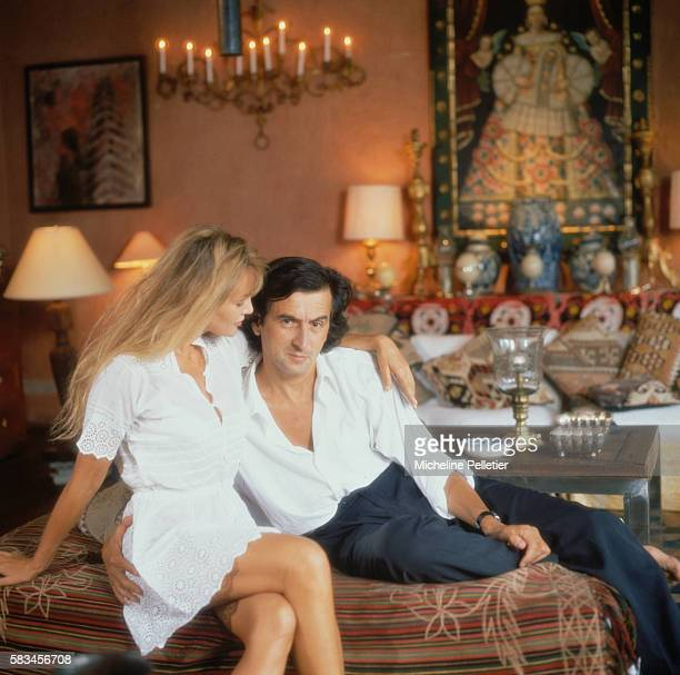 French actress Arielle Dombasle and French philosopher writer and film director BernardHenri Levy sit on a sofa in the living room of their residence...
