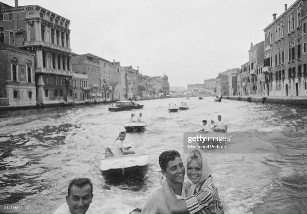 French actress Brigitte Bardot and French singer Sacha Distel (Sacha Alexandre) smiling on a motorboat at the 19th Venice International Film Festival. Venice, August 1958