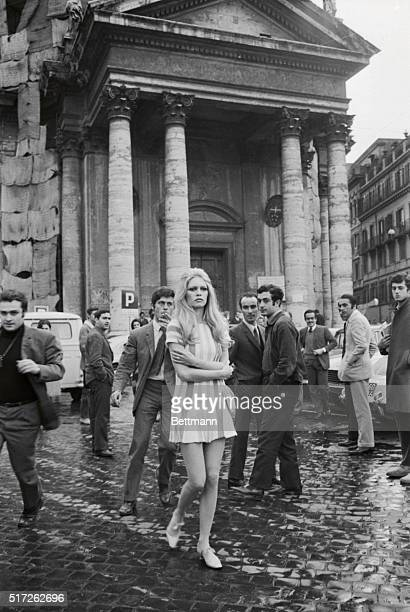 French actress Brigitte Bardot captures the stares of Roman girl watchers as she strolls through the Piazza del Popolo while filming a sequence for...