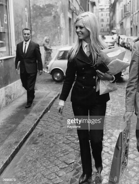 French actress Brigitte Bardot goes shopping in the Via Margutta in Rome wearing a sleek trouser suit.