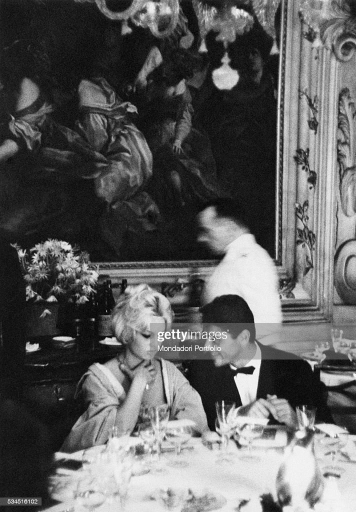 French actress Brigitte Bardot holds a hand on her neck and looks down thoughtfully, seated alongside her new boyfriend, the guitarist Sacha Distel, at a gala dinner held in her honor, the party, organized by film producer Raoul Levy, was set in the ballroom of the patrician Palazzo Barbaro, decorated with baroque stucco works and the Venetian XVIII century paintings. Venice (Italy), 2nd September 1958.