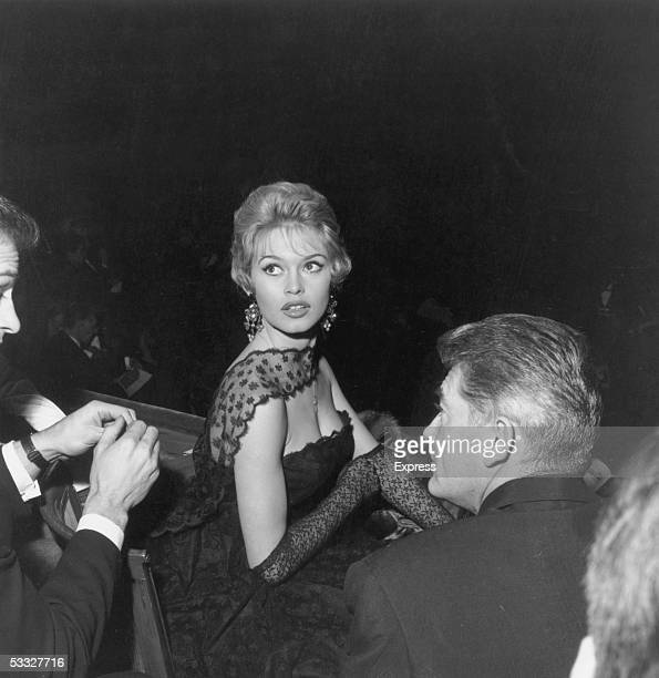 French actress Brigitte Bardot in London 1958 She wears a strapless black evening dress with a lace wrap and long lace gloves