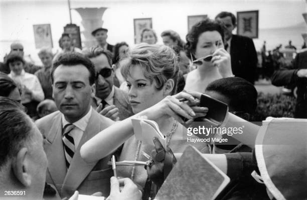 French actress Brigitte Bardot is besieged by fans and autograph hunters at the Cannes Film Festival. Original Publication: Picture Post - 8378 -...