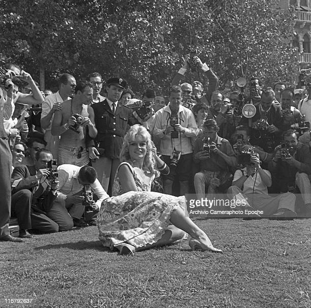 French actress Brigitte Bardot lying on the grass with crossed legs wearing a floral dress posing for the photographers holding cameras mostly...