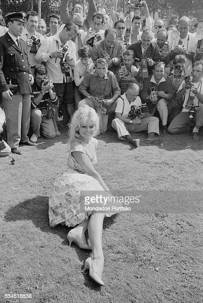 French actress Brigitte Bardot sitting on the grass and being photographed by the journalists at the 19th Venice International Film Festival Venice...