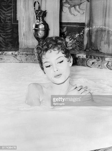 French actress Brigitte Bardot, who portrays Nero's bride, Poppea, in Nero's Big Weekend, relaxes in her milk bath during a sequence in the film in...