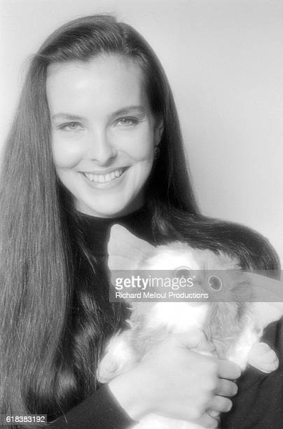 French actress Carole Bouquet holds a stuffed gremlin from the 1984 film Gremlins