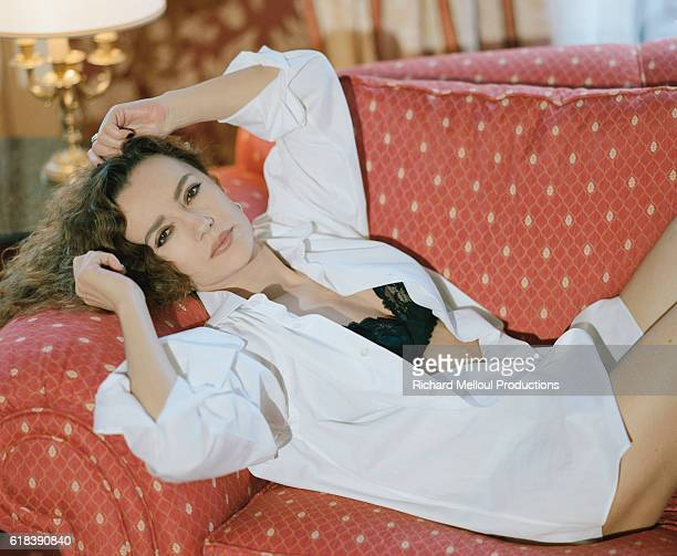 French actress Caroline Cellier reclines on a sofa in her hotel room at Paris Hotel Scribe