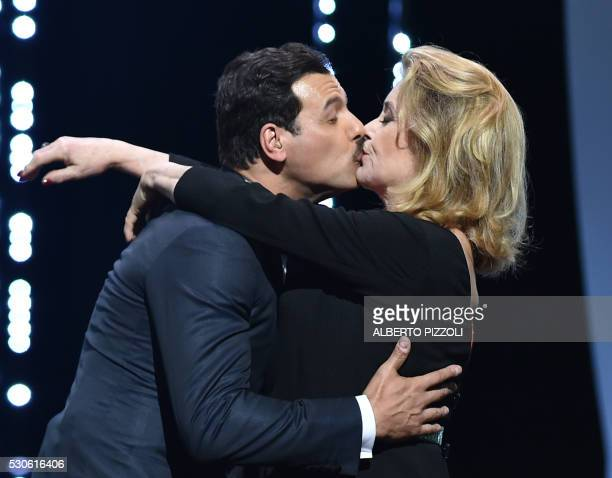 TOPSHOT French actress Catherine Deneuve embraces French actor and Master of Ceremony Laurent Lafitte on stage on May 11 2016 during the opening...