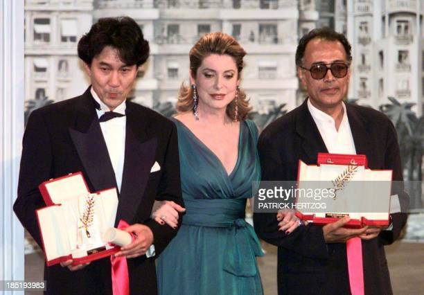 French actress Catherine Deneuve poses with Japanese actor Koji Yakusho representing director Shohei Imamura for the film 'The Eel' and Iranian...