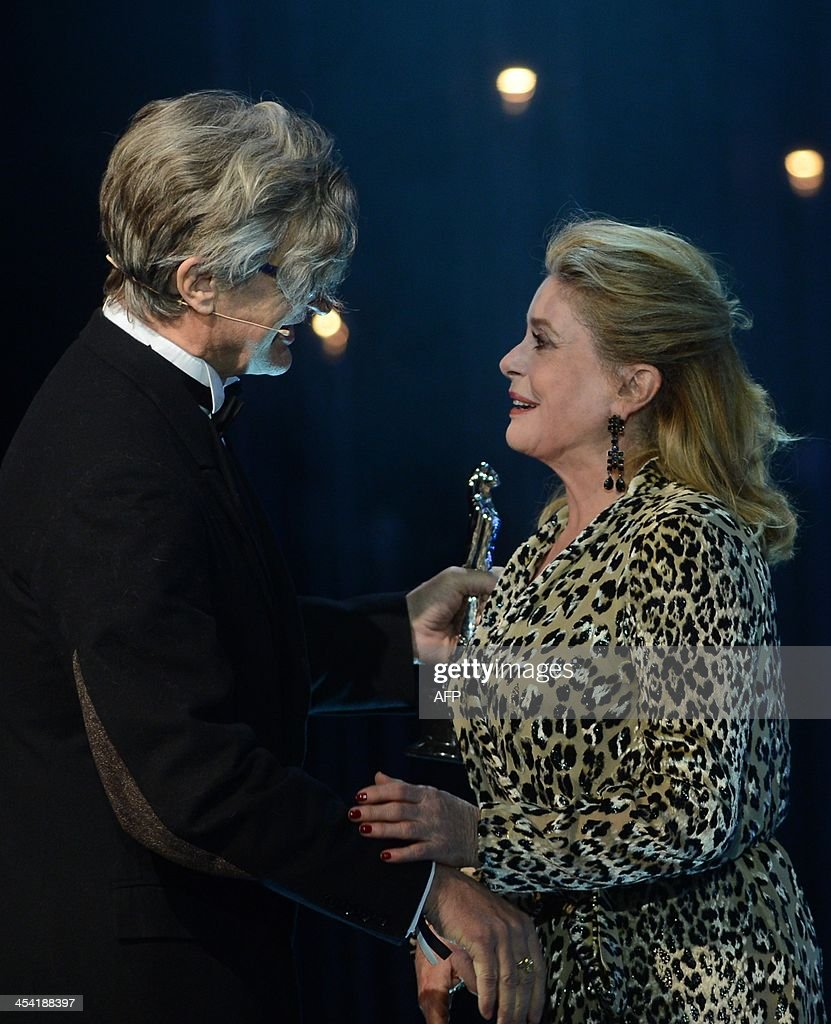 French actress Catherine Deneuve receives her award from German director Wim Wenders (L) at the 26th European Film Awards ceremony on December 7, 2013 in Berlin. Every year, the various activities of the European Film Academy culminate in the ceremony of the European Film Awards. In a total of 21 categories, among them European Film, European Director, European Actress and European Actor, the European Film Awards annually honour the greatest achievements in European cinema.