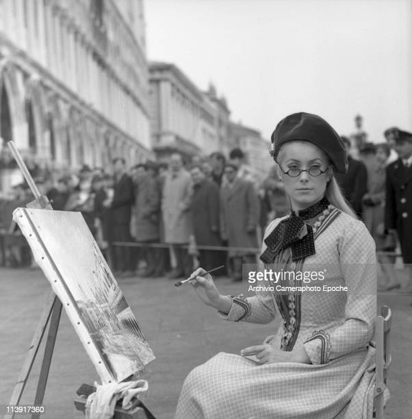 French Actress Catherine Deneuve sitting on a chair in St Mark Square costumed next to an easel with a Square painting on it on the set of the movie...