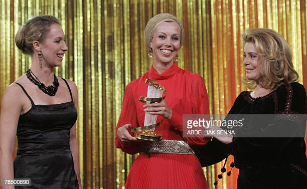 French actress Catherine Deneuve smiles after presenting the Golden Star Award to Estonian producer Katrin Kissa and compatriot actress Tina Tauraite...