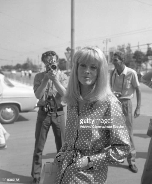French actress Catherine Deneuve wearing a polkadotted dress and holding a handbag portrayed while standing between cameramen and photographers Lido...