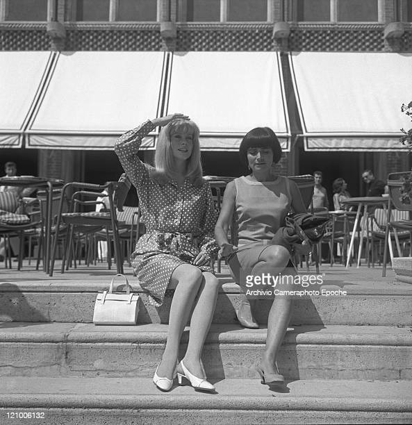 French actress Catherine Deneuve wearing a polkadotted dress portrayed while sitting on the Excelsior Hotel's stairs with the director Agnes Varda...