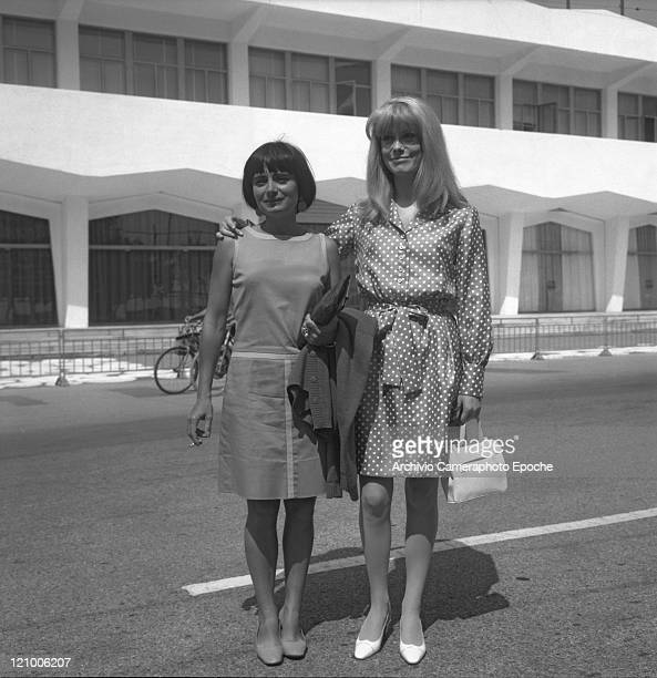 French actress Catherine Deneuve wearing a polkadotted dress portrayed while standing in front of the Movie Festival building with the director Agnes...