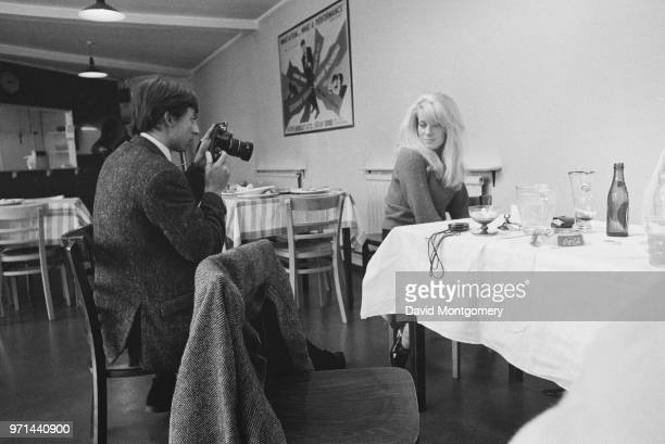 French actress Catherine Deneuve with a photographer during a photo shoot held at a restaurant UK circa 1965