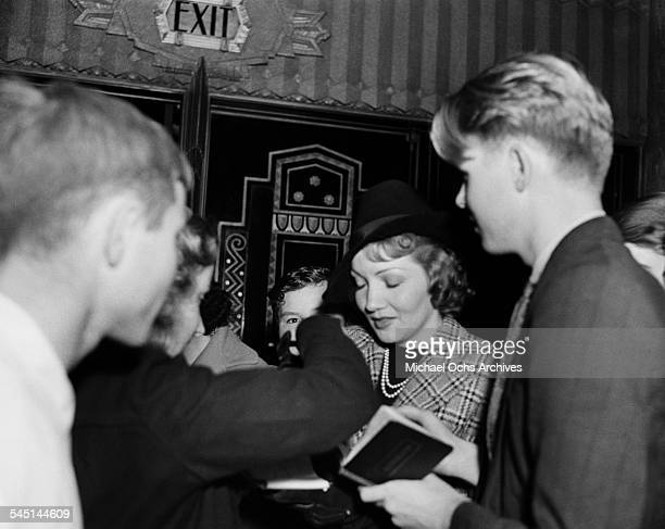 French actress Claudette Colbert autographs for her fans in Los Angeles California