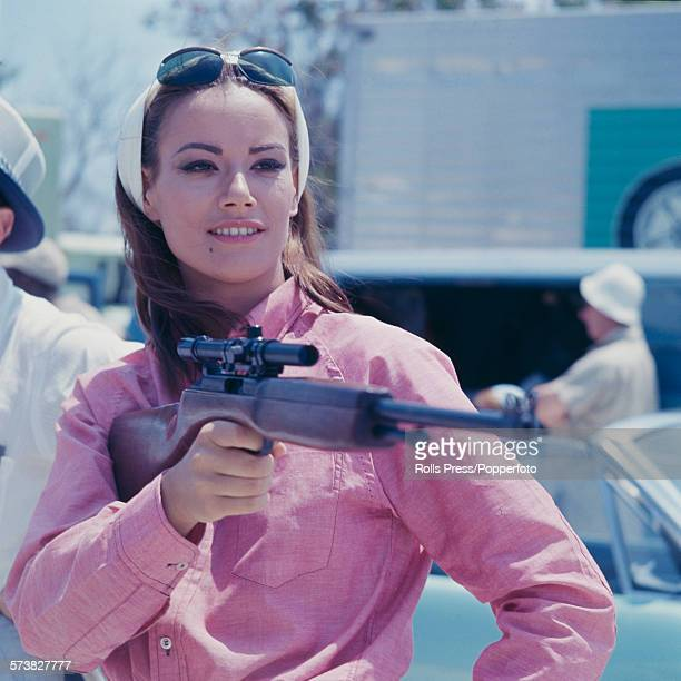 French actress Claudine Auger pictured in character as Domino Derval wearing a pink shirt and holding a rifle during filming of the James Bond film...