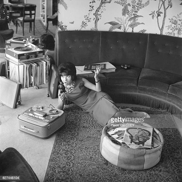 French actress Dany Carrel uses a tape recorder while relaxing at her home in Paris
