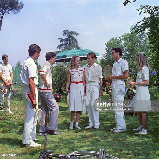 French actress Dominique Sanda Austrian actor Helmut Berger and Italian actor Lino Capolicchio gathered in a garden in a scene from the film The...