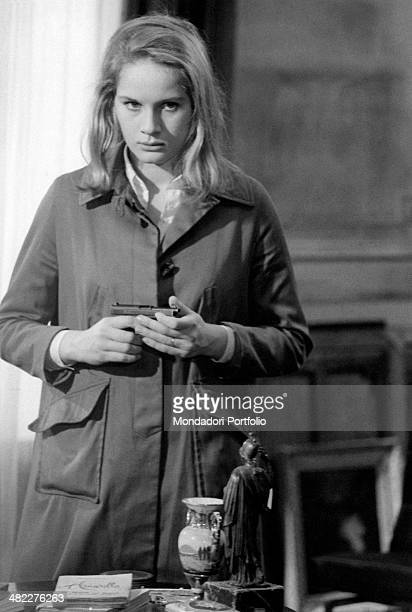 French actress Dominique Sanda holding a gun in the film A Gentle Woman 1969