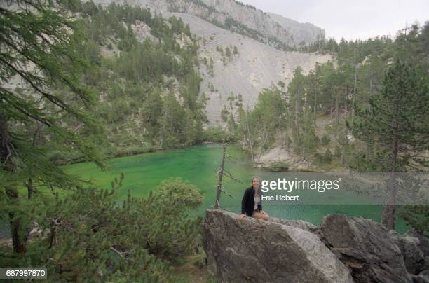 French actress Fanny Cottencon sits on a rock overlooking a secluded mountain lake She is spending her vacation in the HautesAlpes region of France