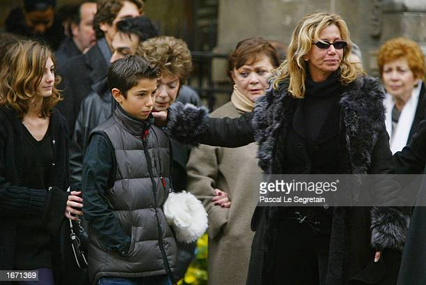 French actress Fiona Gelin holds her son as she leaves the Church of Saint Germain des Pres after the funeral for her father French actor Daniel...
