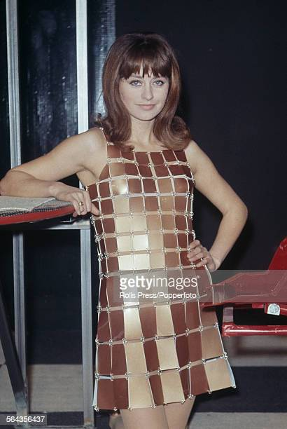 French actress Genevieve Thenier wears a dress composed of small metallic rectangles linked together with wire loops created by French fashion...