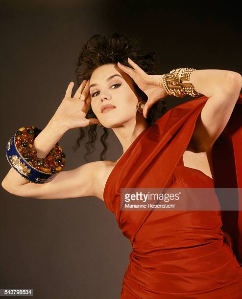 French actress Isabelle Adjani wearing a fruitcake on her arm