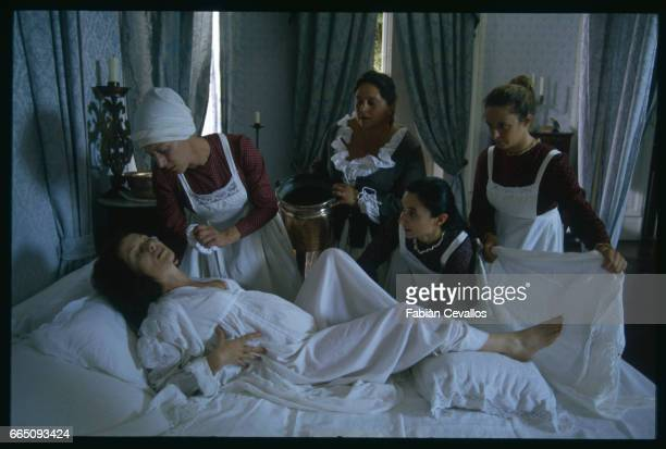 French actress Isabelle Huppert about to give birth to a child lies on her bed with her servants around her in a scene taken from the movie Le...